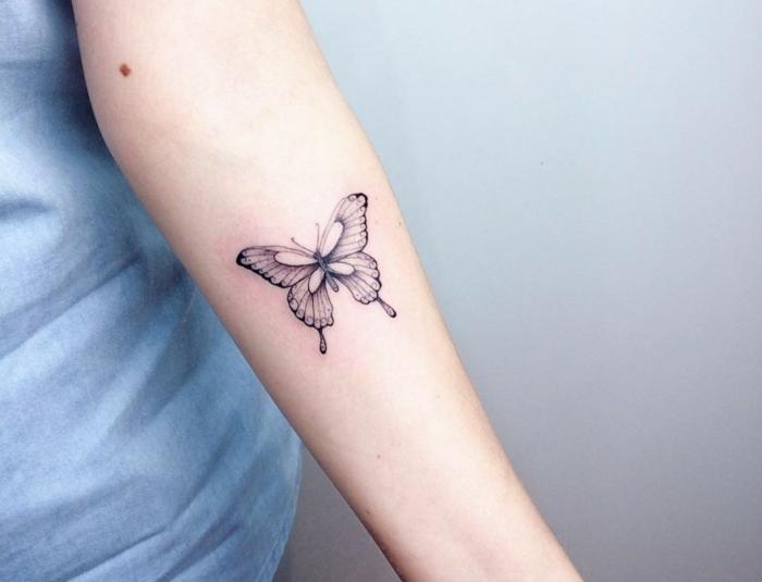 tattoos pequeños en el antebrazo, dibujo de mariposa tinte negro, diseños con significado para mujeres