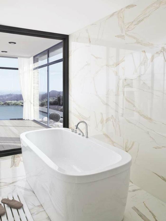 ejemplos de baños modernos con vista, bañera exenta en blanco y paredes y suelo baldosas de mármol