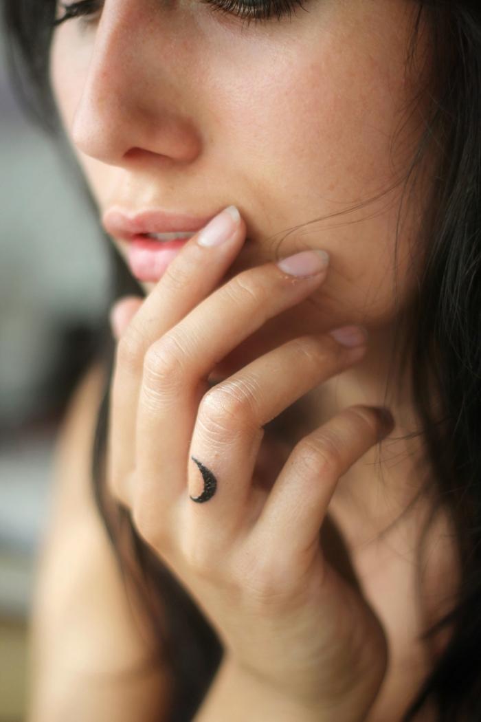 diseños de tatuajes finos para mujer con significado, pequeña luna con tinte negro tatuada en el dedo anular