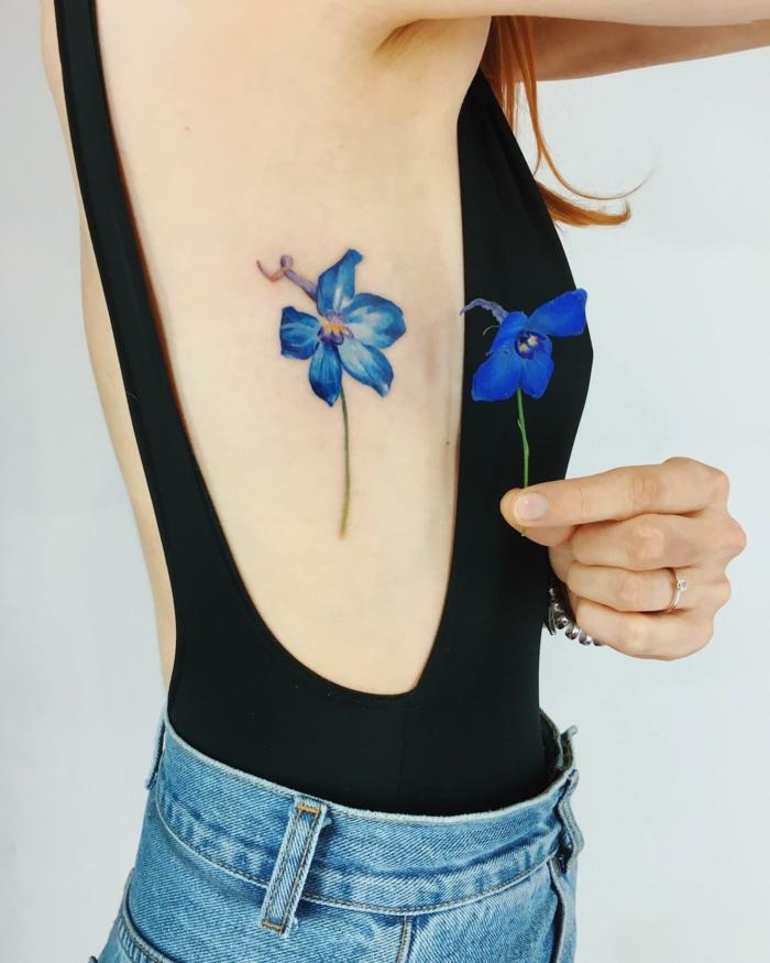 tatuajes simbolicos con flores, preciosa idea de tatuaje femeninos, tatuaje en color azul de tamaño grande, ejemplos de tatuajes con gran significado femeninos