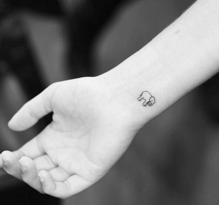 tatuajes minimalistas con significado, tatuajes simbolicos en la muñeca, pequeño elefante tinte negro