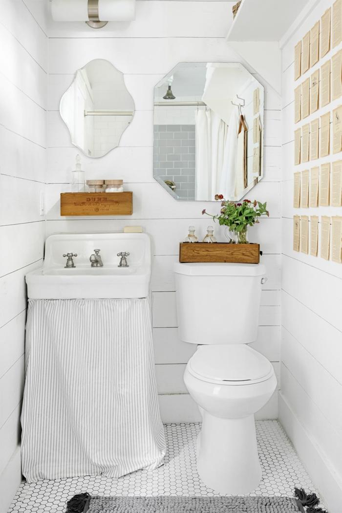 aseos pequeños decorados en blanco con espejos modernos de forma de hexágonos y decoración original