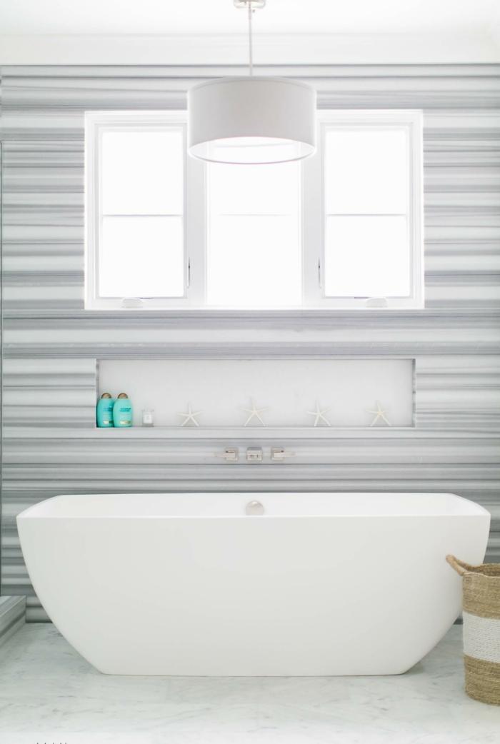 decoracion baños en estilo moderno minimalista, bañera exenta en blanco y paredes en rayas en blanco y gris