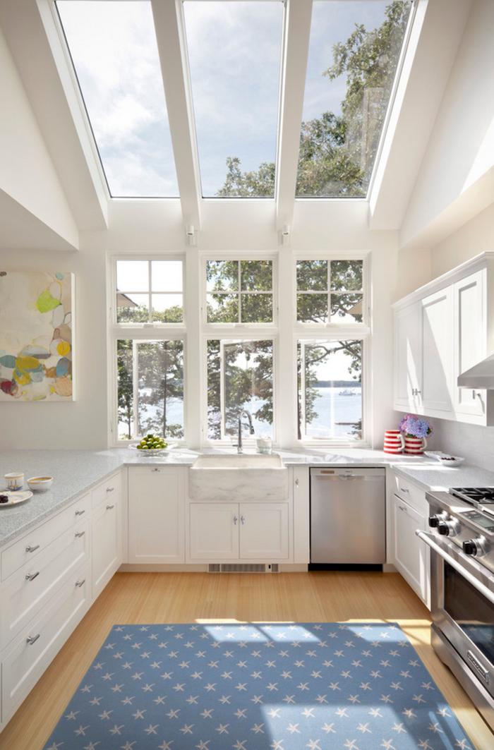 cocina pequeña con ventanas en la pared y en el techo en blanco con alfombra azul, barra americana