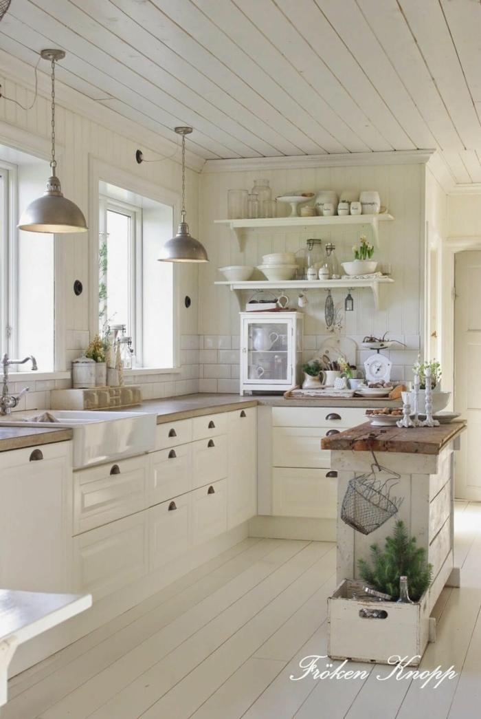 salon cocina en blanco con armarios, techo y paredes en color crema con lamapras de metal colgantes