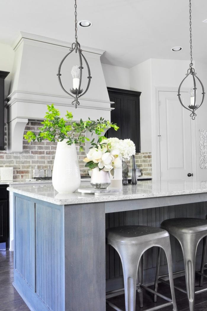cocina con isla de madera en azul con encimera en blanco y jarron con flores vivas encima, barras de cocina