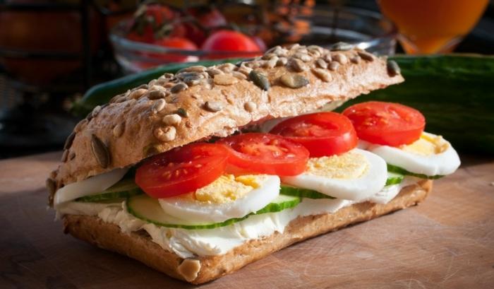 desayunos fitness con huevos cocidos, bocadillo simple con tomates, pepinos, queso crema y pan integral con semillas