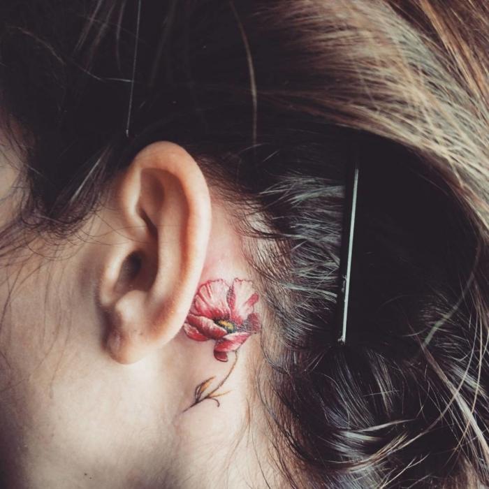 preciosa flor en color rojo tatuada detrás de la oreja, diseños de tatuajes delicados y femininos