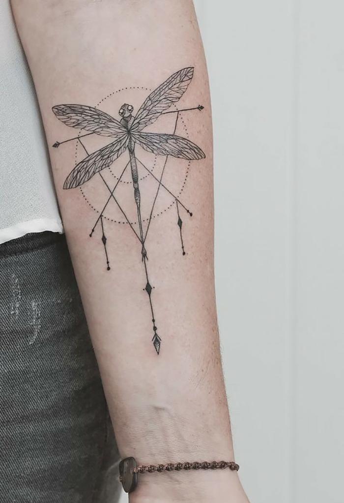 precioso diseños de tatuajes sombolicos, libélula tatuada en el antebrazo en una esfera