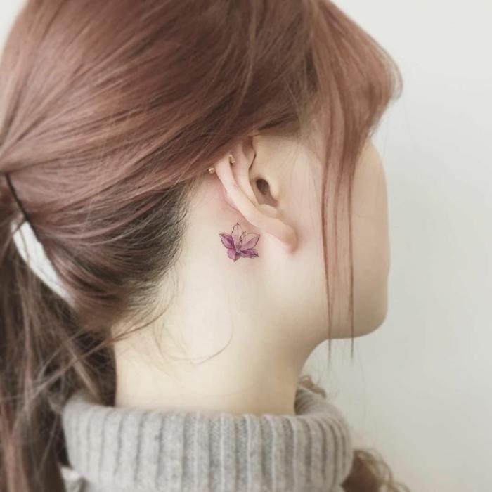 tattoos pequeños detrás de la oreja, tatuaje delicado y bonito de una flor en color lila, ideas de tattoos femeninos