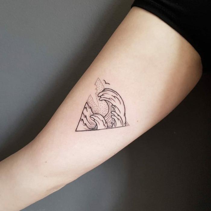tatuajes de triangulos con significado, tatuaje minimaslita en el brazo, triángulo con olas del mar