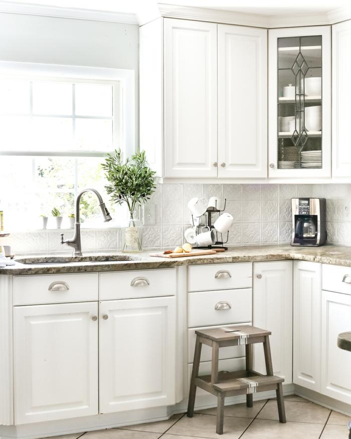 parte de la cocina donde se ve la ventana con los armarios en blanco y una esclera de cocina de madera