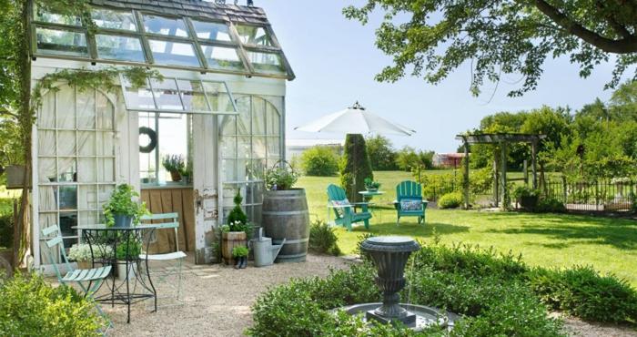jardines rusticos organizados de maravilla, suelo con césped y gravilla, precioso fuente decorado con arbustos ornamentales