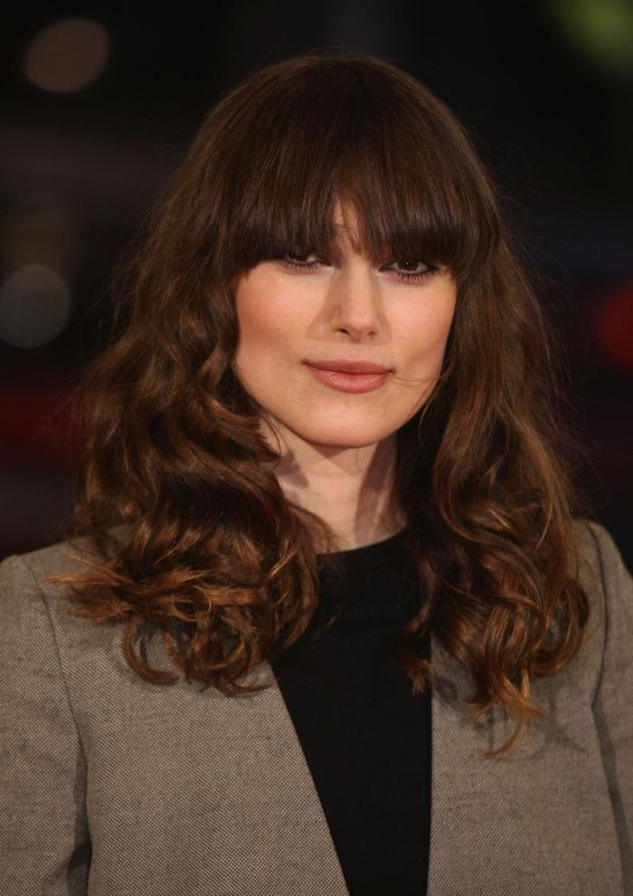 Keira Knightley con media melena rizada con flequillo recto, cortes de pelo mujer modernos