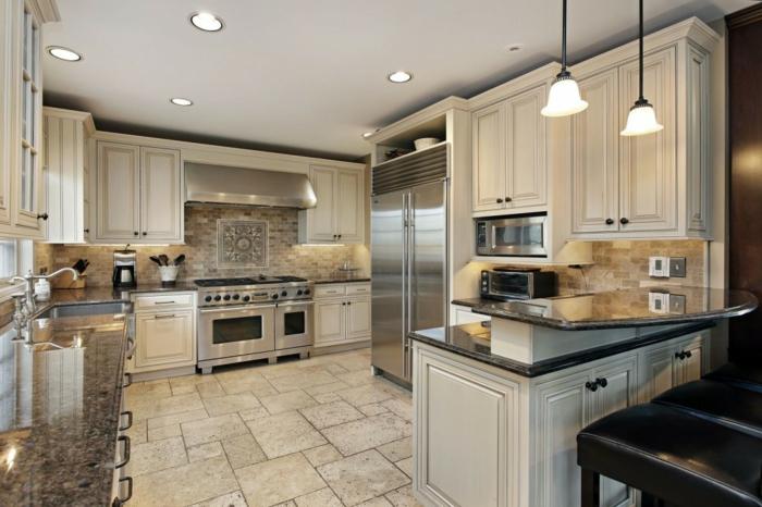 cocina con armarios en color beige de alto coste con azulejos y lamparas de lunares, barra americana cocina