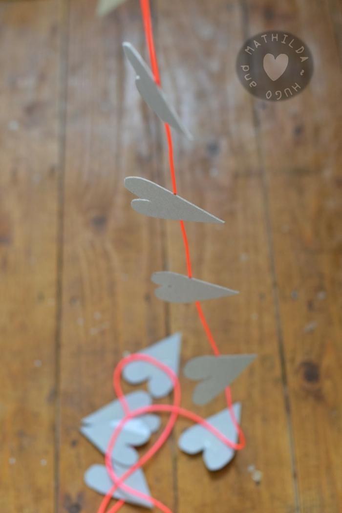guirnalda decorativa DIY, diy manualidades originales, hilo color naranja y figuras en forma de corazón