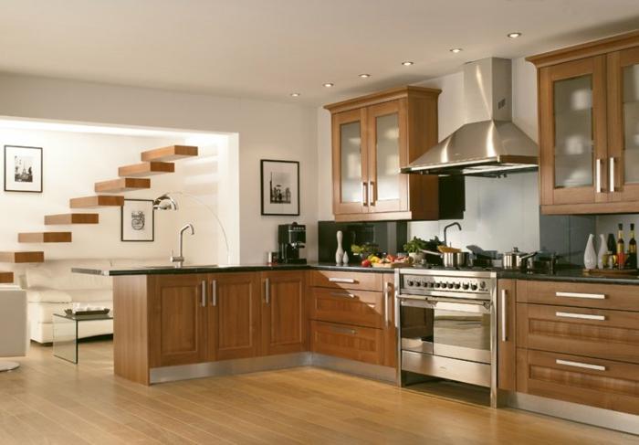un lado de la cocina americana con armarios de madera con vista al salon y a las escaleras de la casa