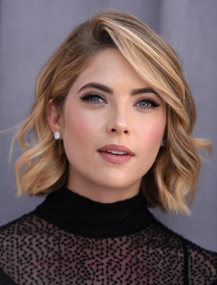 como cortar el pelo corto a una mujer, con melena midi rubia y con ondulaciones y vestido con cuello alto y con transparencia en negro