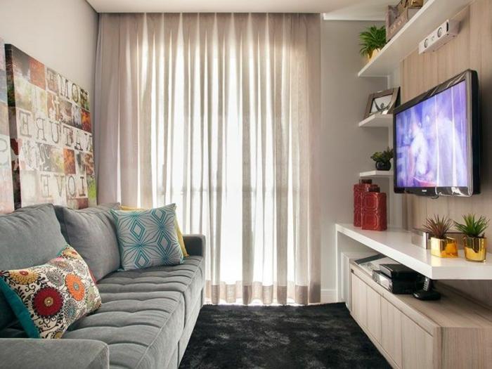 decoracion salon pequeño con sofa gris, alfombra negra de pelo, cortinas en color crema y televisor en la pared