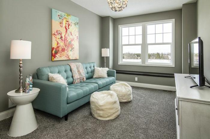 decoracion salon pequeño, sofa de cuero azul con otomanas de pelo blanco y alfombra en marron claro
