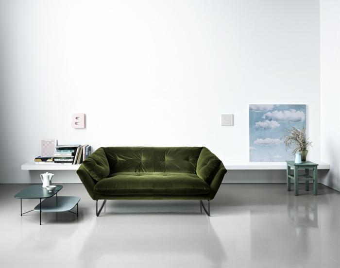 decoracion salon pequeño con sofa de terciopelo en color verde oliva con mesas pequeñas y bajitas y suelo gris clarito