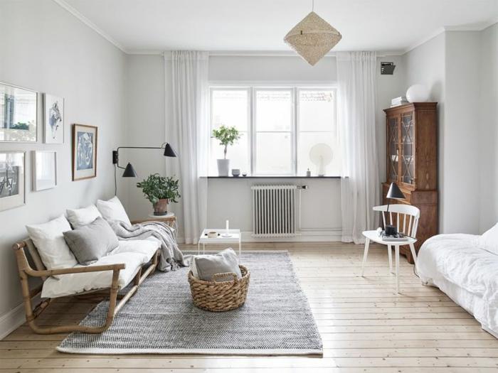 decoracion salon pequeño con alfombra en gris, sofa de madera con cojines blancos y cuadros en la pared