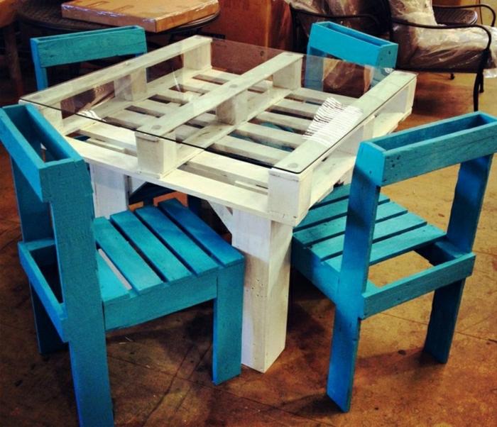 meas de comer blanca alta hecha con palets y con vidrio encima, sillas azules, como hacer una mesa