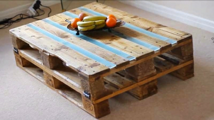 como hacer una mesa de madera, de palets con detalles azules y sujeta con visagras de metal en los cuatro lados