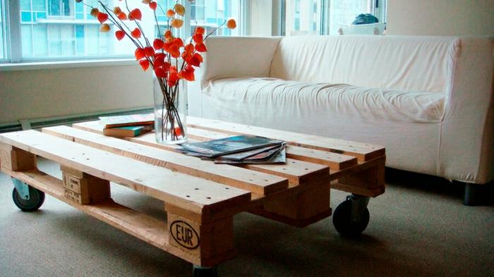 mesa con ruedas de palets lijada, sin pintar hecha para el salón con jarron de vidrio encima, como hacer una mesa