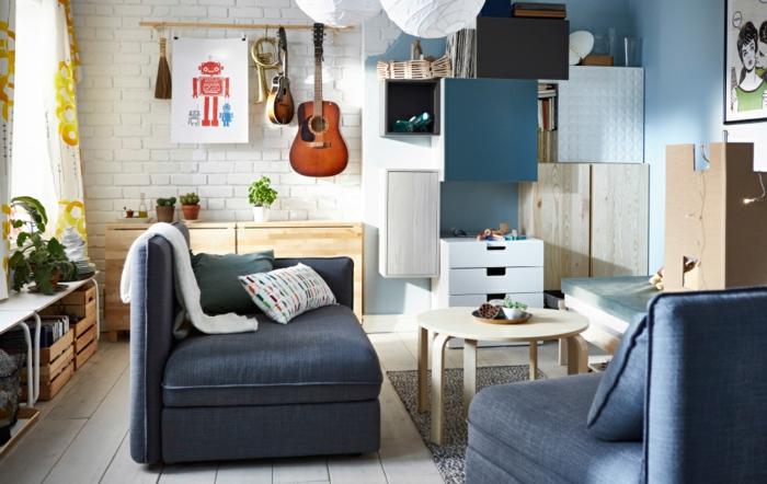 decoracion salon comedor rectangular con sofas en color azul con mesa redonda de madera