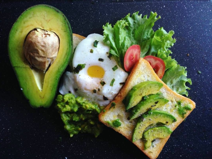 ricas propuestas de desayunos con aguacate, tostadas con trozos de aguacate, huevos fritos, lechuga y tomates