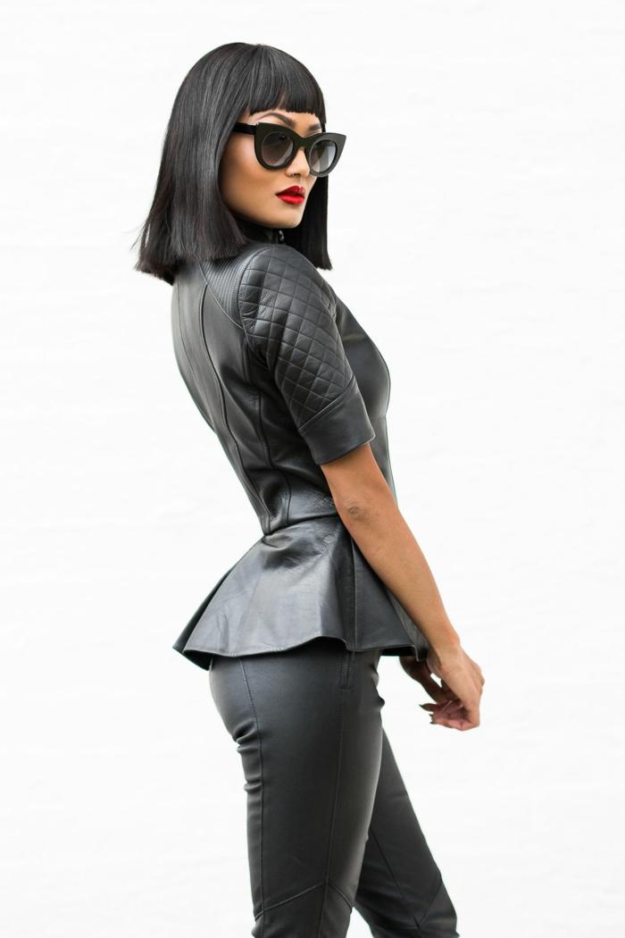cortes de pelo chica, modelo con melena negra con flequillo de ultima tendencia en la moda de los peinados, vesida con chaqueta con volantes y pantalones de cuero