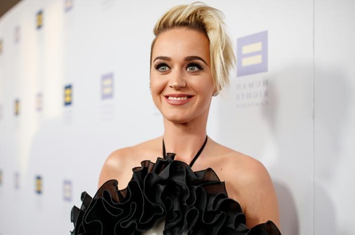 cortes de pelo mujer cara alargada, Katy Perry con corte de pelo el pixie, con mechas rubias y vestido negro con abundancia de volantes