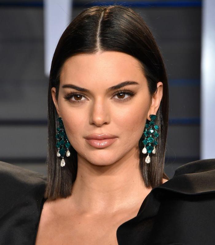 cortes de pelo mujer cara alargada, Kendall Janner, con media melena sin flequillo y estilosamente peinada con peindientes grandes en verde