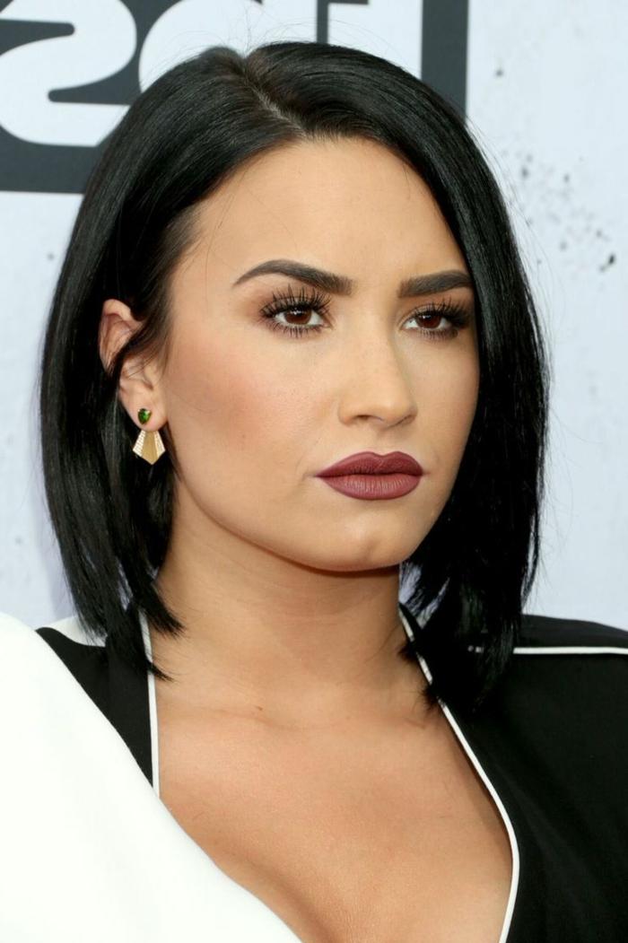 cortes de pelo mujer segun rostro, Demi Lovato con media melena sin flequillo negra, con maquillaje de noche, con labial rojo oscuro