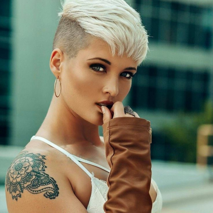 cortes de pelo mujer segun rostro, modelo con pelo de color perla estilo pixie rapado por la parte de atrás y con pendientes de aro