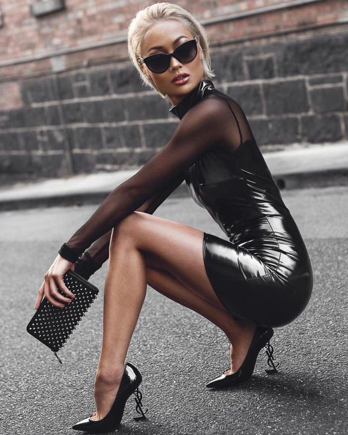cortes de pelo para mujer, modelo con melena midi rubia con vestido negro de cuello alto y transparencias con mangas largas y tacones