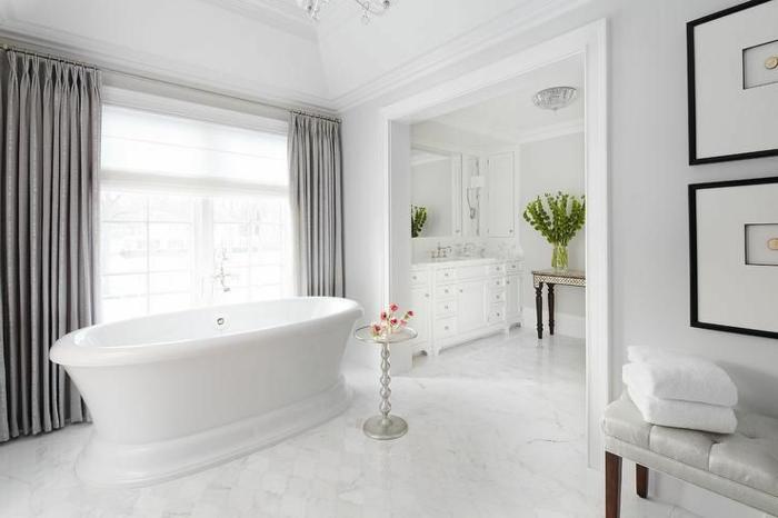 cuartos de baño modernos decorados enteramente en blanco, cortinas en plateado, suelo de marfil y decoración cuadros en la pared