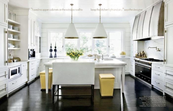 cocina blanca con tres ventanas y mesa blanca con tres taburetes amarillos y suelo en color marron