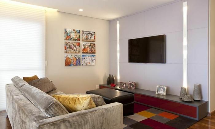 decoracion salon comedor rectangular con cuadros en la pared y televisor con alfombra de muchos colores