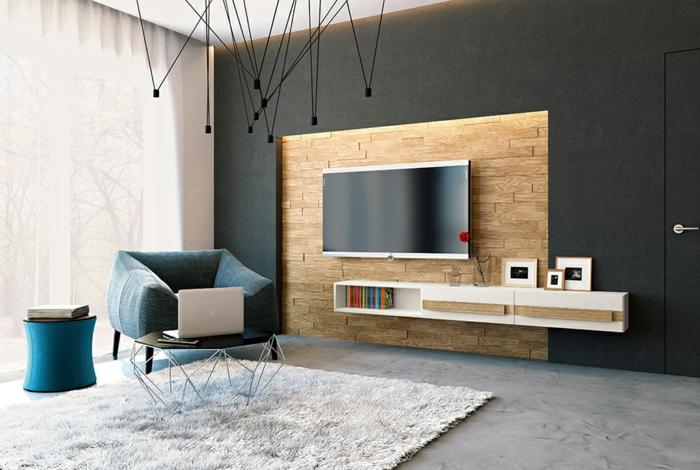 decoracion salon pequeño, sillon de un asiento en azul oscuro con alfombra de pelo gris clarita y televisor en la pared