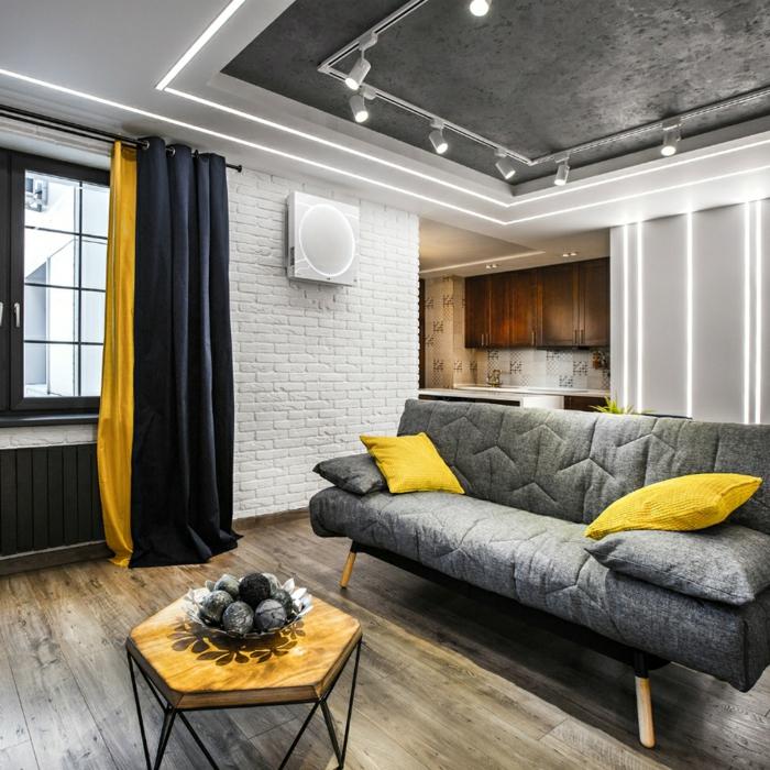 decoracion salon pequeño, sofa gris con cojies en color mostaza con mesa de madera y hierro y cortinas en negro y mostaza