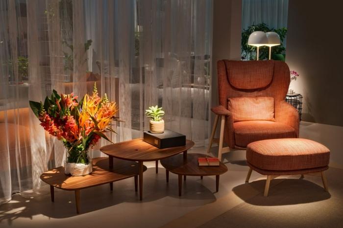 decoracion salon pequeño, sala de estar pequeña con sillon y taburete en color coral con cojin, mesas de madera de diferentes formas