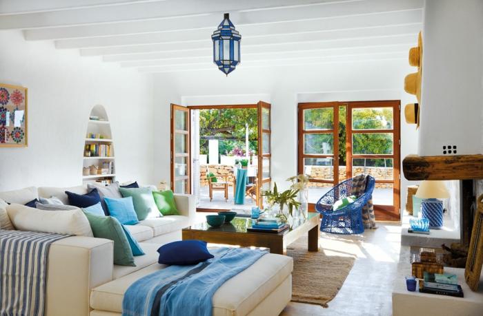 decoracion salon pequeño con sofa blanco con muchos cojines de diferentes colores y mesa rectangular de madera con alfombra marron clara
