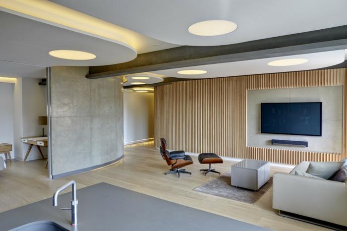 decoración salon moderno con televisor en la pared y sillon de masaje con taburete de cuero negro