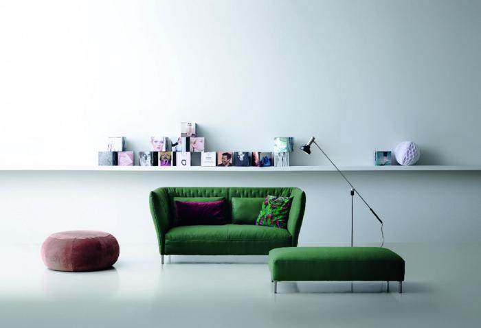 decoracion salon pequeño, sillon de doble asiento en color verde oliva con cojines en lila oscuro y verde con flores, otomana de color lila pastel