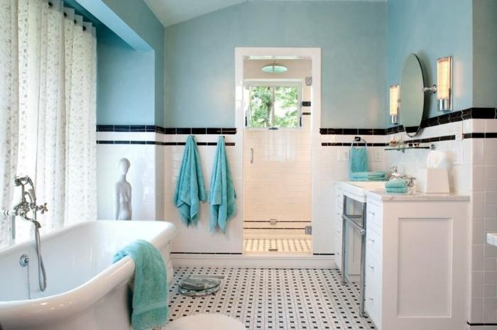decoracion baños pequeños en blanco y azul, techo inclinado, suelo con azulejos en blanco y negro y bañera moderna