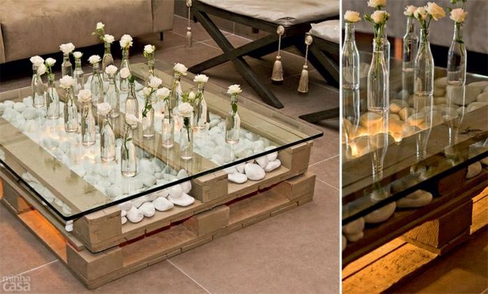 mesa con dos palets uno encima del otro, sin ruedas y con vidrio, decorada con piedras y flores en botellas