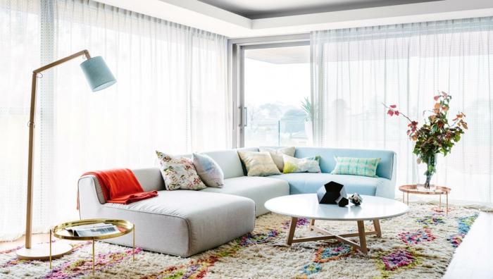 decoracion salon pequeño moderno, con sofa ovalado y lampara de pie en color azul clarito, mesa redonda de madera