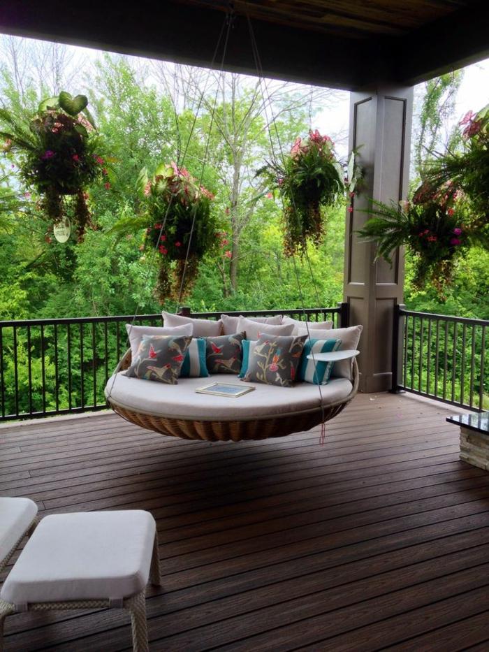 diseño jardines, hamaca grande redonda que sirve como columpio colgada del techo con cojines multicolor